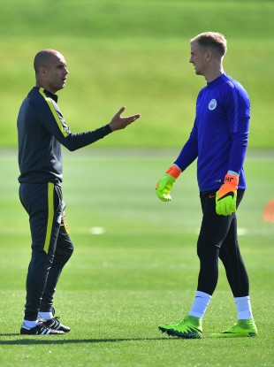 Manchester City manager Pep Guardiola talks to goalkeeper Joe Hart during a training session last August.