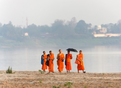Buddhist monks walk on the Mekong river's bank in Vientiane, Laos (2012).