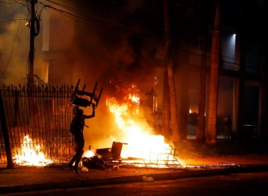 A protester carries a chair to a fire outside the congress building