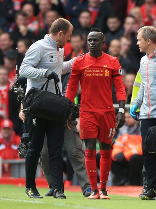 Liverpool's Sadio Mane leaves the pitch after picking up an injury.