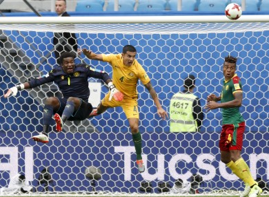 Cameroon goalkeeper Fabrice Ondoa, Australia's Tim Cahill and Cameroon's Adolphe Teikeu in action.