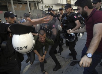 Riot police detain a person as they attempt to disperse activists
