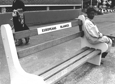 A young black man sitting on a bench reserved for white people in South Africa in 1959