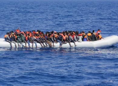 Refugees and migrants are seen floating in an overcrowded rubber boat.