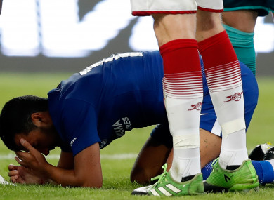 Pedro down holding his face.