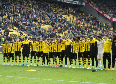 The Borussia Dortmund team stand before the jersey of Marc Bartra, injured in the attack.