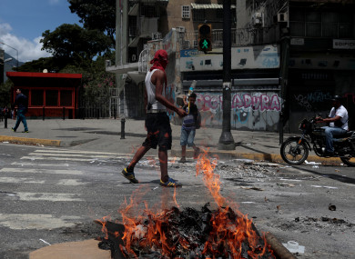 A demonstrator blocks a street during a rally against Venezuela's President Nicolas Maduro's government in Caracas.