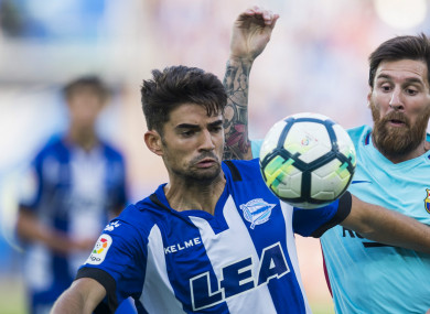 Alaves' Enzo Zidane (left) competes for the ball with Lionel Messi.