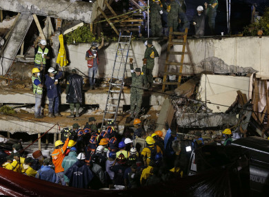 Rescue personnel work on the rescue of a trapped child at the collapsed Enrique Rebsamen primary schoool
