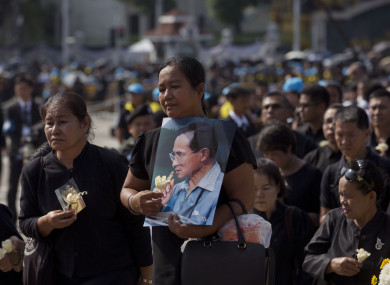 Thai mourners stand in a line to pay respect to a portrait of late Thai King Bhumibol Adulyadej.