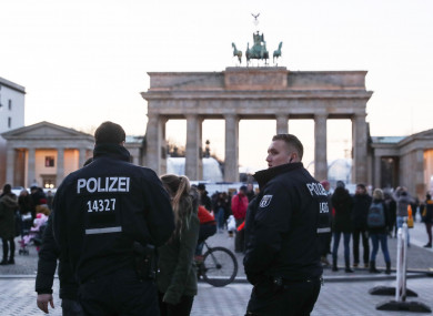 Two policemen stand guard in front of the Brandenburg Gate in Berlin.
