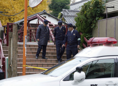 Police officers walk near the scene of the shrine.