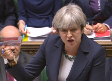 Theresa May holds up a Labour Party leaflet in the Commons during PMQs.