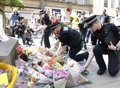 Police laying flowers in St Ann's Square, Manchester, the day after the bombing