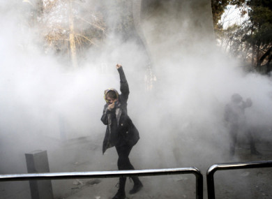 A university student attends a protest inside Tehran University earlier this week while a smoke grenade is thrown by anti-riot police.