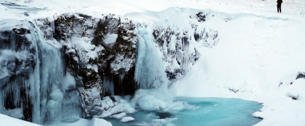 People walk around the frozen five meter high Kirjufell waterfall on the west coast of Iceland.