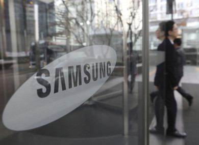 An employee walks past a logo of the Samsung Electronics Co. at its office in Seoul, South Korea.