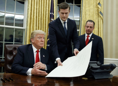 White House staff secretary Rob Porter hands President Donald Trump a confirmation order