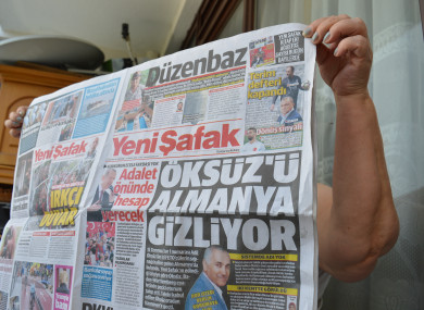 A woman holds a copy of Turkish pro-government daily newspaper