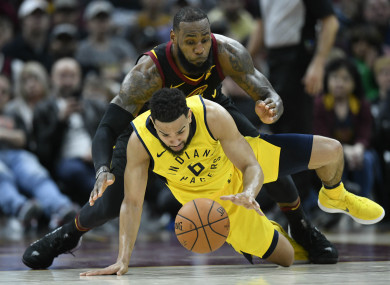 LeBron James and Indiana Pacers guard Cory Joseph reach for a loose ball in the fourth quarter in game one of the first round of the 2018 NBA Playoffs.