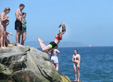 Mary Kate Kiernan from Trim Meath jumps into the sea at the Forty Foot in Dublin during the sunny hot weather.