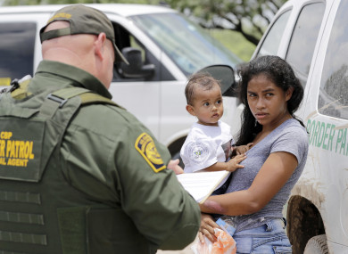 A woman from Honduras with her child surrendering to US border patrol agents.