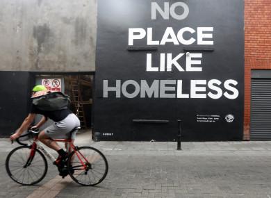 A member of the public passing a mural on Camden Row, Dublin, highlighting homelessness