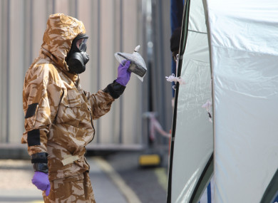 An investigator in a chemical suit removes items as they work behind screens erected in Rollestone Street, Salisbury, Wiltshire.