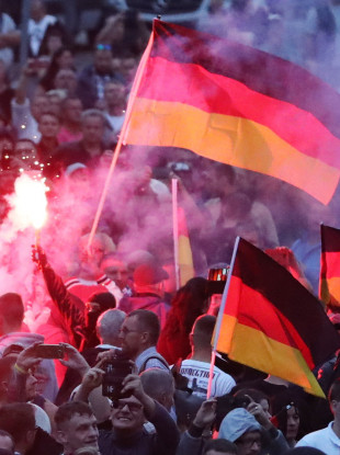 Demonstrators of the right-wing scene ignite pyrotechnics and wave flags of Germany