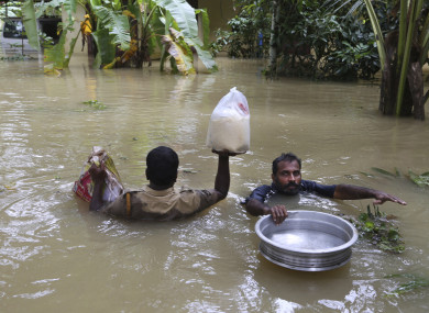 An Indian policeman, left, and a volunteer carry essential supplies for stranded people in a flooded area in Chengannur.