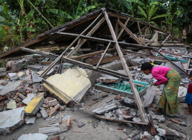 A woman search her belongings at ruins of her houses after an earthquake hit on Sunday in North Lombok, Indonesia on Wednesday, 8 August