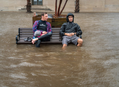 Chris Craig and Zach Boucher sit on a bench following Hurricane Florence.