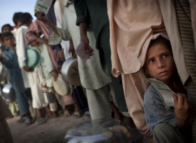 A young Pakistani boy displaced by flooding holds his ration card as he tries to push as they line up for hot meal