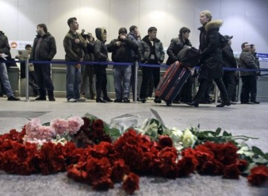 A woman pushes her luggage past flowers at the site of Monday's explosion at Domodedovo.