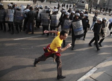 A demonstrator runs past a line of riot police in Cairo, Egypt, on Tuesday, 25 January 2011.