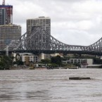 Debris floats down the river under the Story Bridge in Brisbane, Australia, 13 January 2011. (AP Photo/Tertius Pickard)