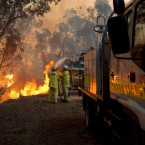 In this Sunday, Feb. 6, 2011, photo provided by the Fire and Emergency Services Authority of Western Australia, Gosnell bushfire brigade battles a fire at the rear of a house in the Perth, suburb of Roleystone. (AP Photo/FESA, Evan Collis)