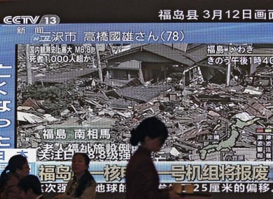 A hostess at China's National People's Congress, in Beijing, passes a TV screen showing the damage to the Japanese prefecture of Fukushima, home to the stricken Fukushima I nuclear plant.
