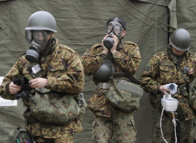 Members of the Japan Self-Defense Forces wearing protective gear get ready for radioactive decontamination operations in Nihommatsu, near the Fukushima I plant.