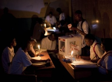 Electoral workers count ballots by candlelight in Haiti last night.