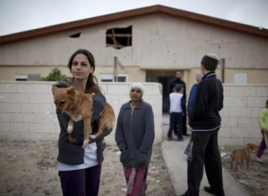 Israeli citizens stand next to a house in Beersheba, damaged by rockets fired by Palestinian militants today.