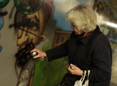 Irmela Mensah-Schramm sprays over a swastika sign in Berlin.
