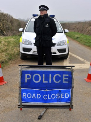 A policeman pictured near the site where the two bodies were found in Gloucestershire.