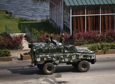 Troops supporting former president Laurent Gbagbo drive past in a armoured car in the city of Abidjan.