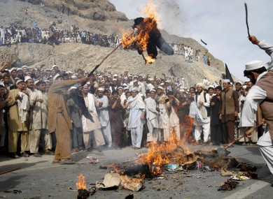 An Afghan protestor, right, hits the burning effigy of the American pastor, Terry Jones during a demonstration in Shinwar, Nangarhar province of Afghanistan on Monday