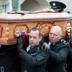 The coffin of PSNI Constable Ronan Kerr is carried through his home town of Beragh in Co Tyrone, to the Church of the Immaculate Conception by colleagues.