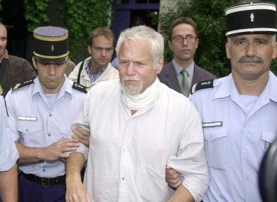 Ira Einhorn is escorted by police in Champagne-Mouton in Central France in July 2001