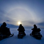People on skidoos admire a nimbus, an optical phenomenon produced by ice crystals in cirrus clouds on the island of Spitsbergen in the Arctic circle during 'midnight sun' season. Image: PA Images/Ben Birchall