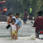 Residents wade through flood waters Nakorn Sithamarat Province, south Thailand. Pic: AP Photo/Sumeth Parnpetch.