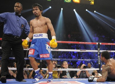 Manny Pacquiao is directed to his corner by referee Kenny Bayless, left, after knocking down Shane Mosley in the third round during a WBO welterweight title bout.